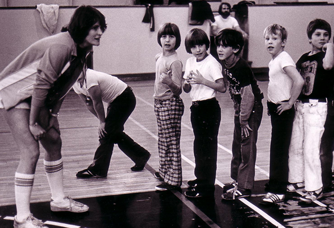 Teacher leading a PE class circa 1979
