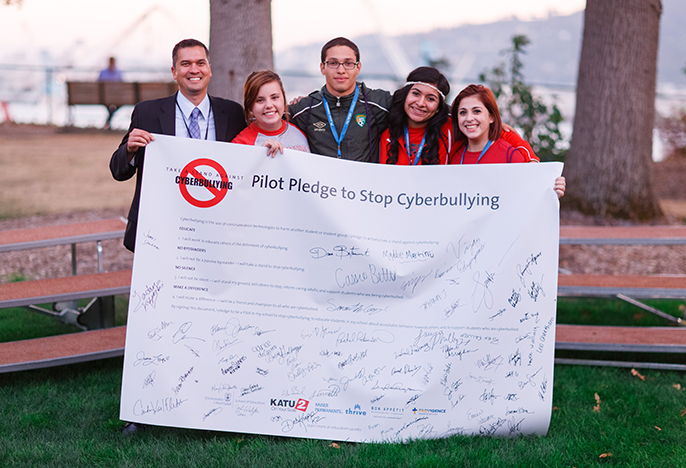 4 four students and a professors holding a banner: Pilot Pledge against Cyberbullying